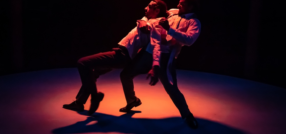 One man falls backwards, and the other behind him catches his fall. The photo is dark, but is lit with a slight red, yellow and purple hue.