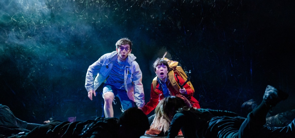 A young boy in a blue coat and a woman in a red coat with a yellow rucksack are on stage, in a forest, with shocked expressions on their face as two performers in all-black crawl in front of them.