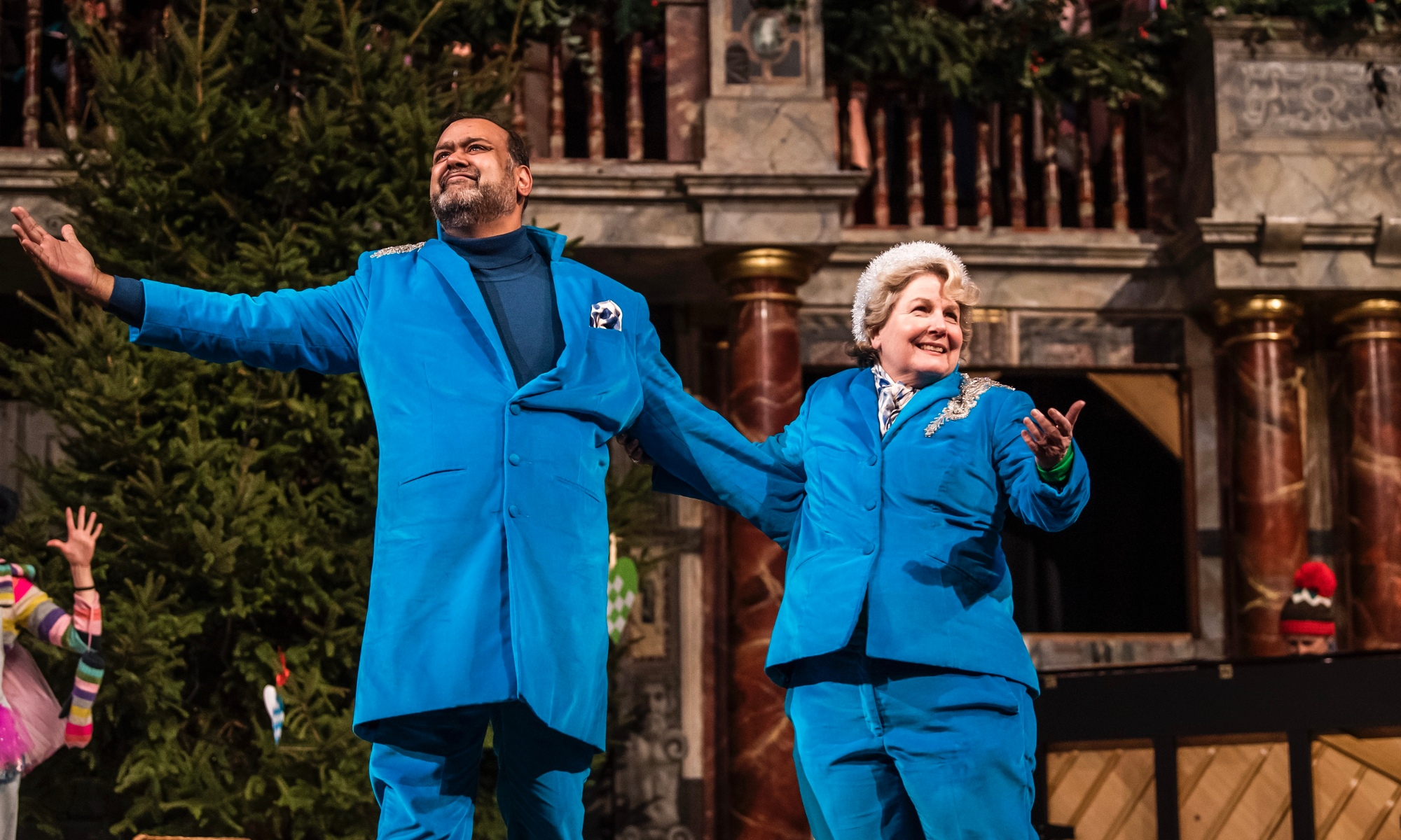 Tony Jayawardena and Sandi Toksvig wearing all blue suits at the Globe. A Christmas tree is on the stage behind them.