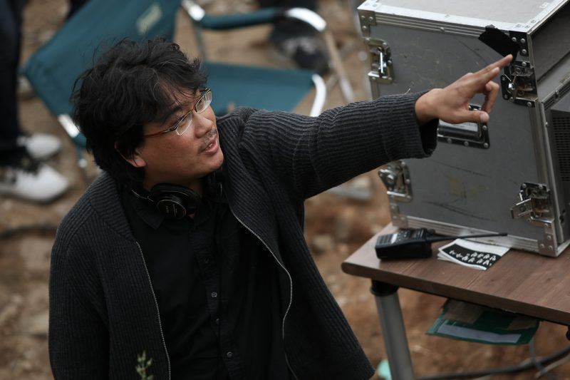 Bong Joon Ho in all-black clothing and with headphones around his neck points at something off-screen.