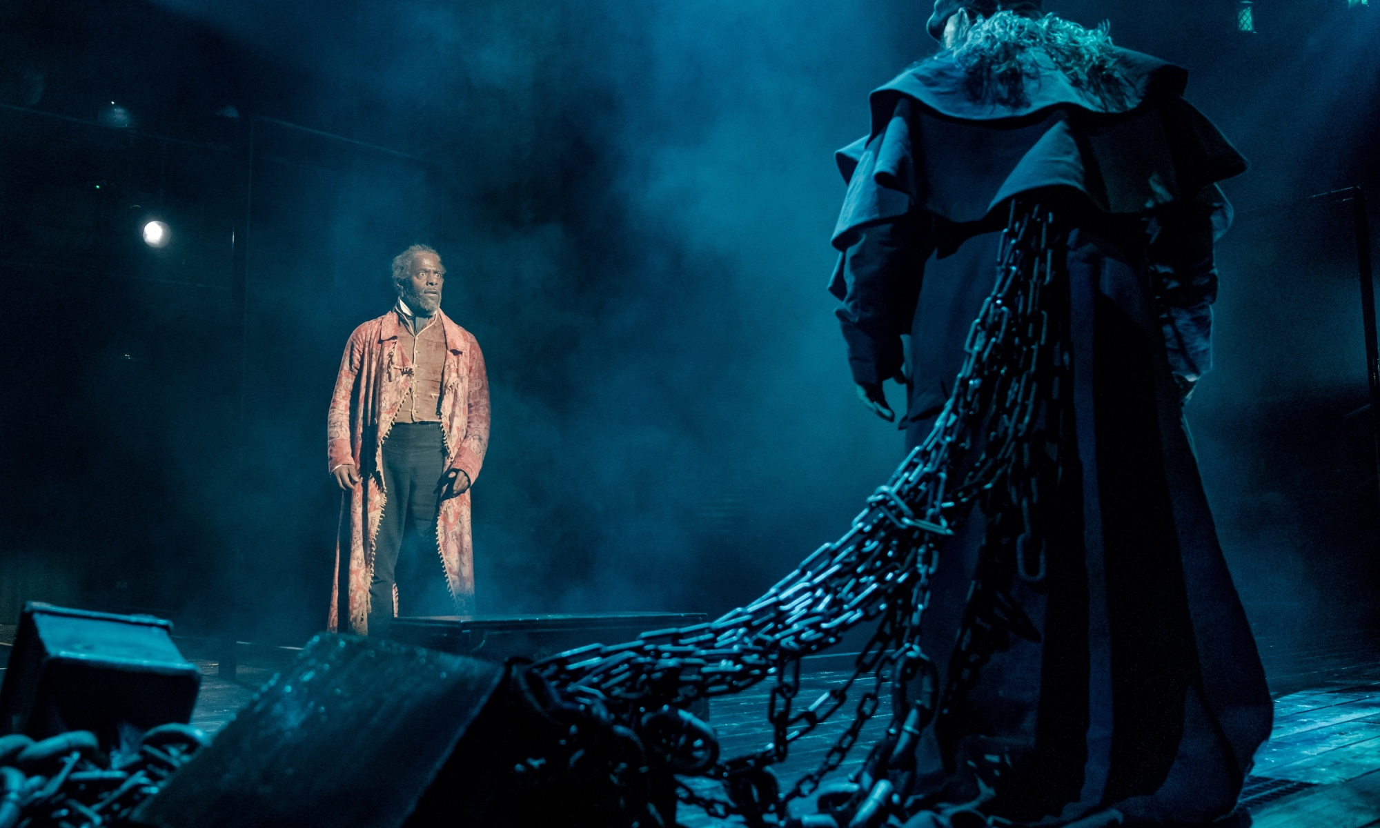 Jacob Marley has his back to the camera, which has chains coming out of it. He's talking to Scrooge, who is at the other end of the stage, with a shocked expression on his face.