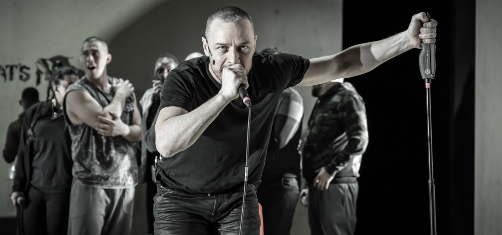 James McAvoy with a shaved head wears all-black clothing and speaks into a microphone. In his left hand, he is gripping the microphone stand.