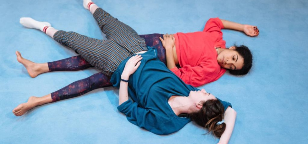 View from above of a woman lying down on a blue carpet. They are wearing a red shirt and purple gym trousers. Another woman is laying on top of her, wearing a blue shirt and multicoloured trousers.