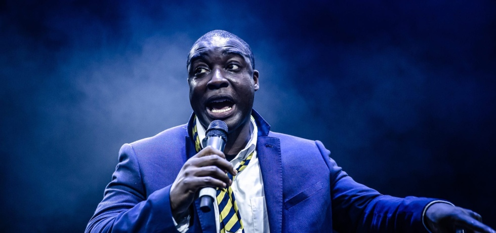 A man in a blue suit, with a white collared shirt and yellow striped tie, speaks into a microphone which he holds in his right hand. The photo has a blue hue to it.