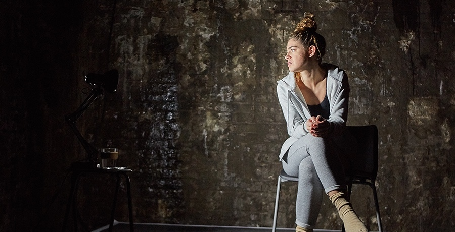 A woman in a grey fleece and grey trousers sits backwards on a chair, looking with disgust at something to the right, the same direction which the light in the photo is coming from.