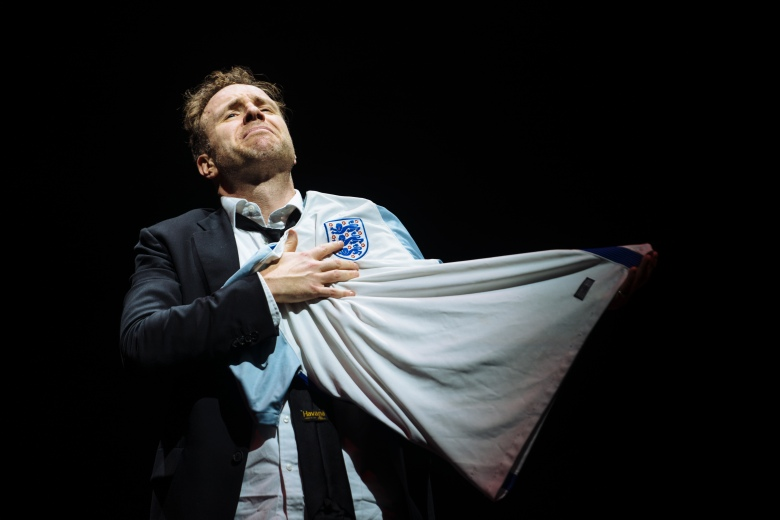 Rafe Spall wears a black suit and white collared shirt. He appears emotional as he holds an England shirt close to his chest.