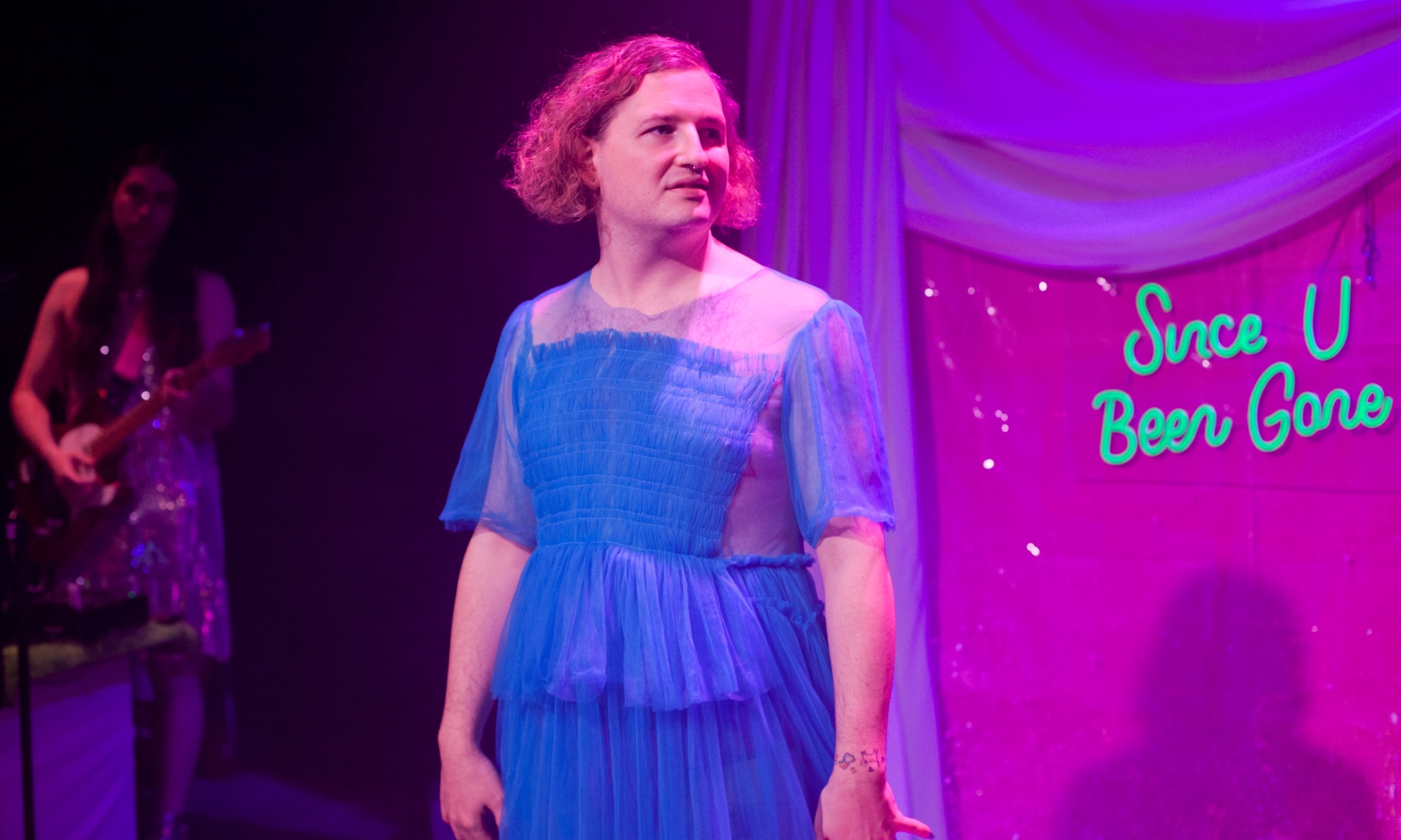 A person in a blue skirt stares at something to their left. Behind them are pink curtains and a wall with the words 'Since U Been Gone' in a green neon sign.