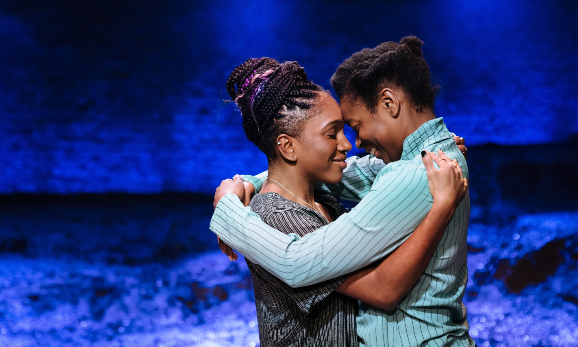 Two black women are holding each other close and smiling. The lighting in the background behind them is a dark blue. They are clearly in love.