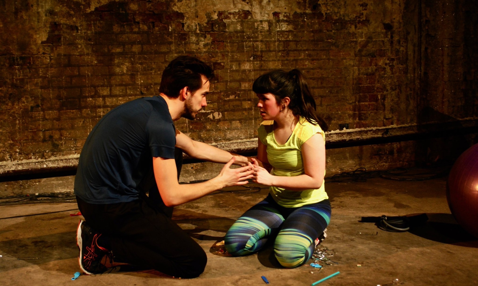 A woman in a yellow shirt and jogging bottoms kneels on the floor. Her hands are held by a man in a black shirt and black jeans. They are both looking at each other, the man with a serious facial expression. A brick wall is behind them.