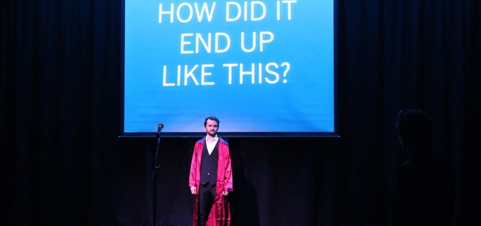 A man in a suit and a red cape stands on a stage. Behind him is a projector screen which displays the words 'How did It end up like this?'