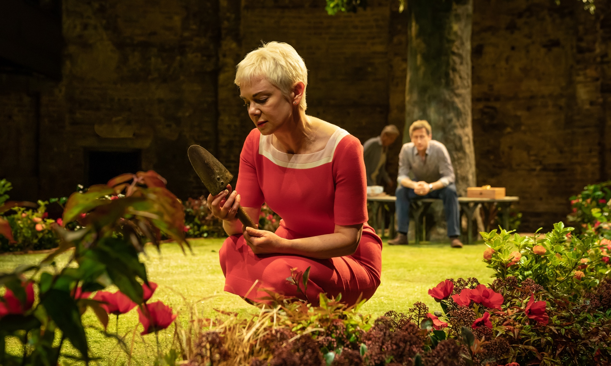 A woman wearing a red dress is in a garden holding a trowel. Flowers are all around her. In the background is a tree, and a man sits down on the wooden seating surrounding it.