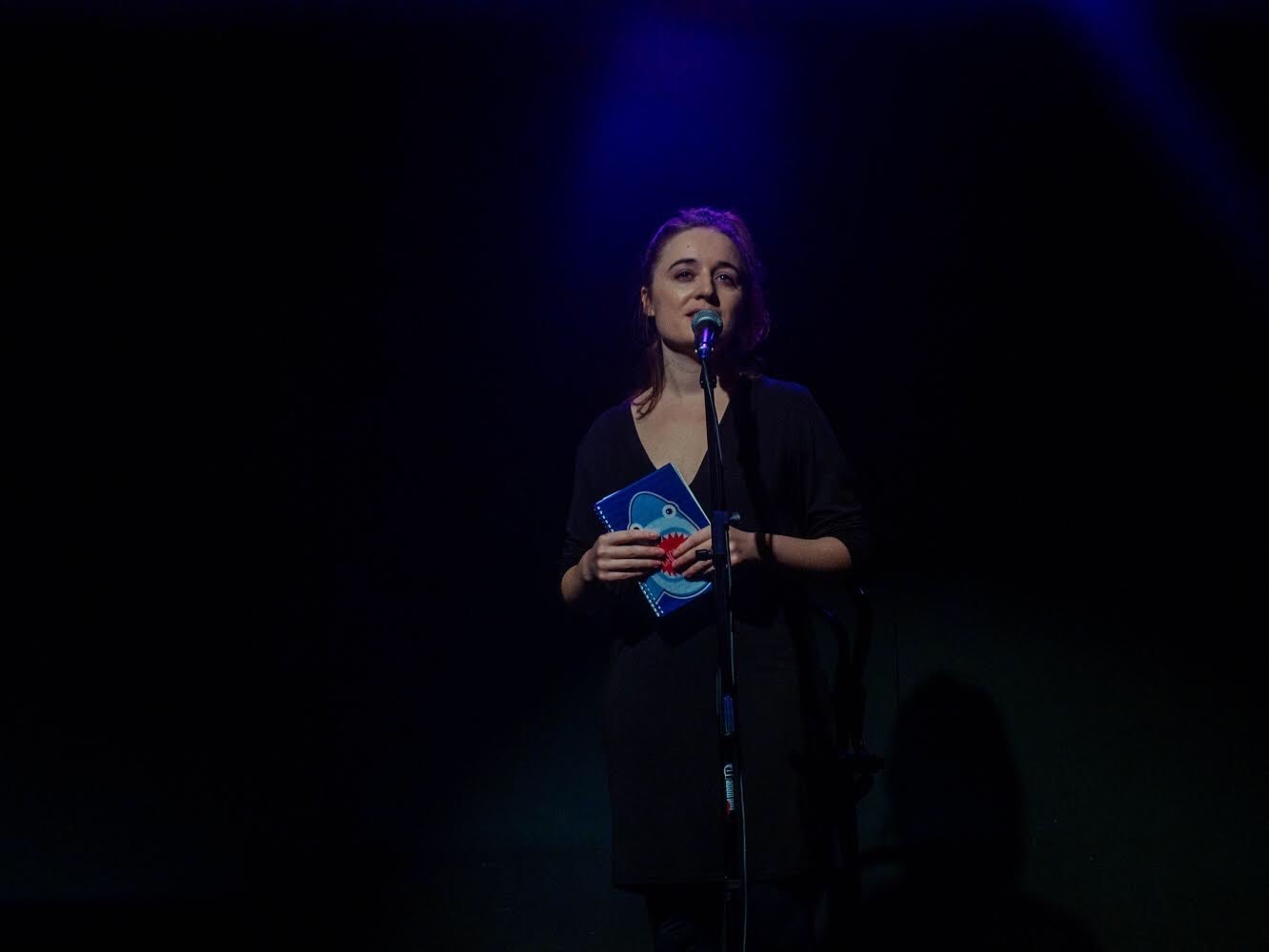 A woman stands behind a microphone, she is holding a blue notebook in her hands.