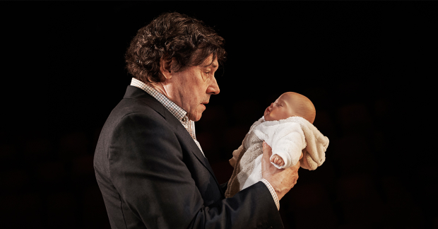 A man with curly hair wearing a suit and white collared shirt holds a baby doll in his hands.