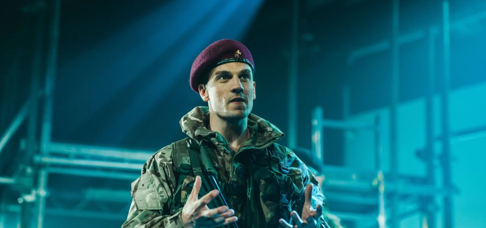A man in camouflage clothing with a red soldier beret has his arms open in front of him. He looks like he is addressing the audience.