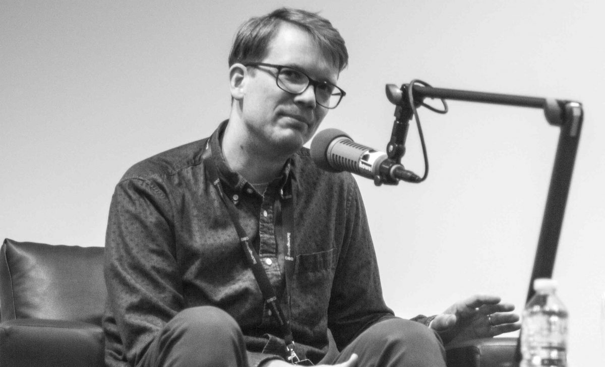Black and white photo of Hank Green seated behind a microphone stand.