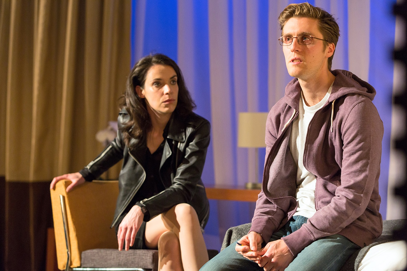 A woman in a black jacket sits crossed legged on a wooden chair. Just in front of her, to the right, is a man with a light purple hooded fleece, glasses and jeans, resting on the edge of a hotel room bed.