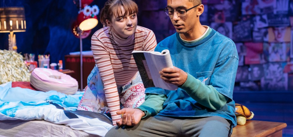 A man in a blue jumper sits on a wooden table and reads from a book. A girl is to the left of him, sitting on the edge of her bed and staring at him with admiration. They are in a bedroom.