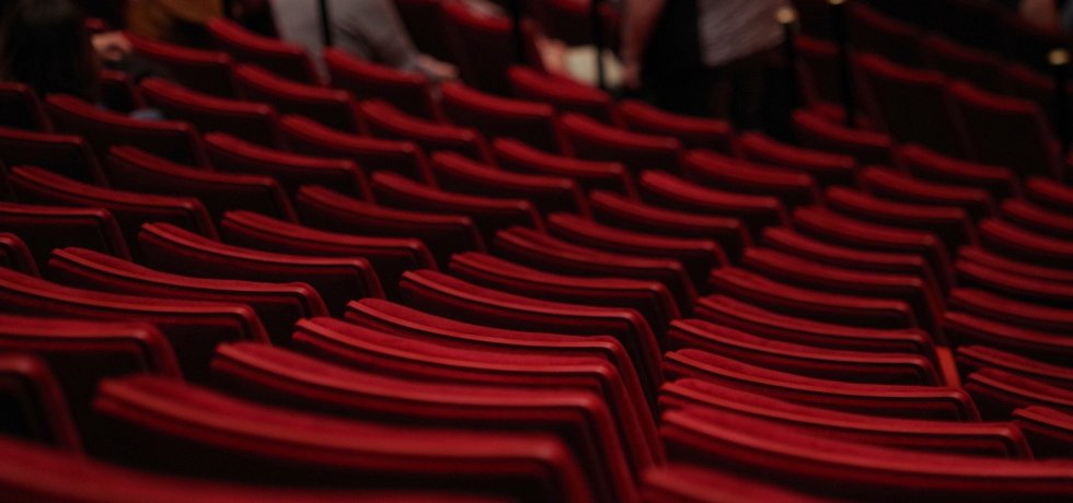 Several rows of red theatre stalls.