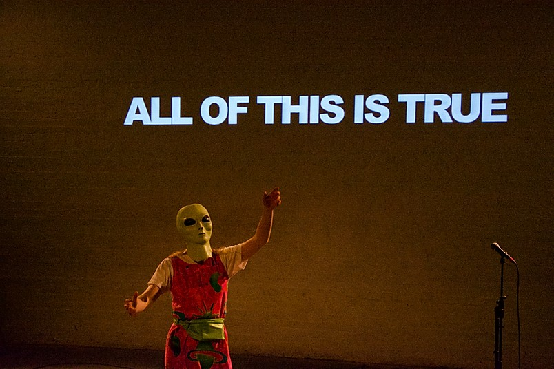 A person in red and yellow clothes dances whilst wearing a green alien mask. Behind them, projected onto the wall are the words 'All of this is true'.
