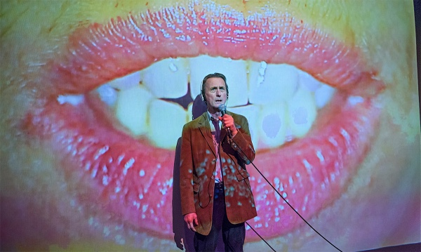 A man in a brown coat stands holding a microphone. Projected on the wall behind him are a set of lips, opened to display the person's white teeth.