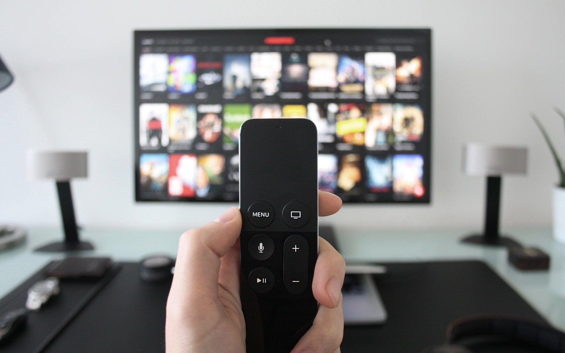 Person holding a TV remote in their hand. Behind that is a TV with the Netflix home screen on it.
