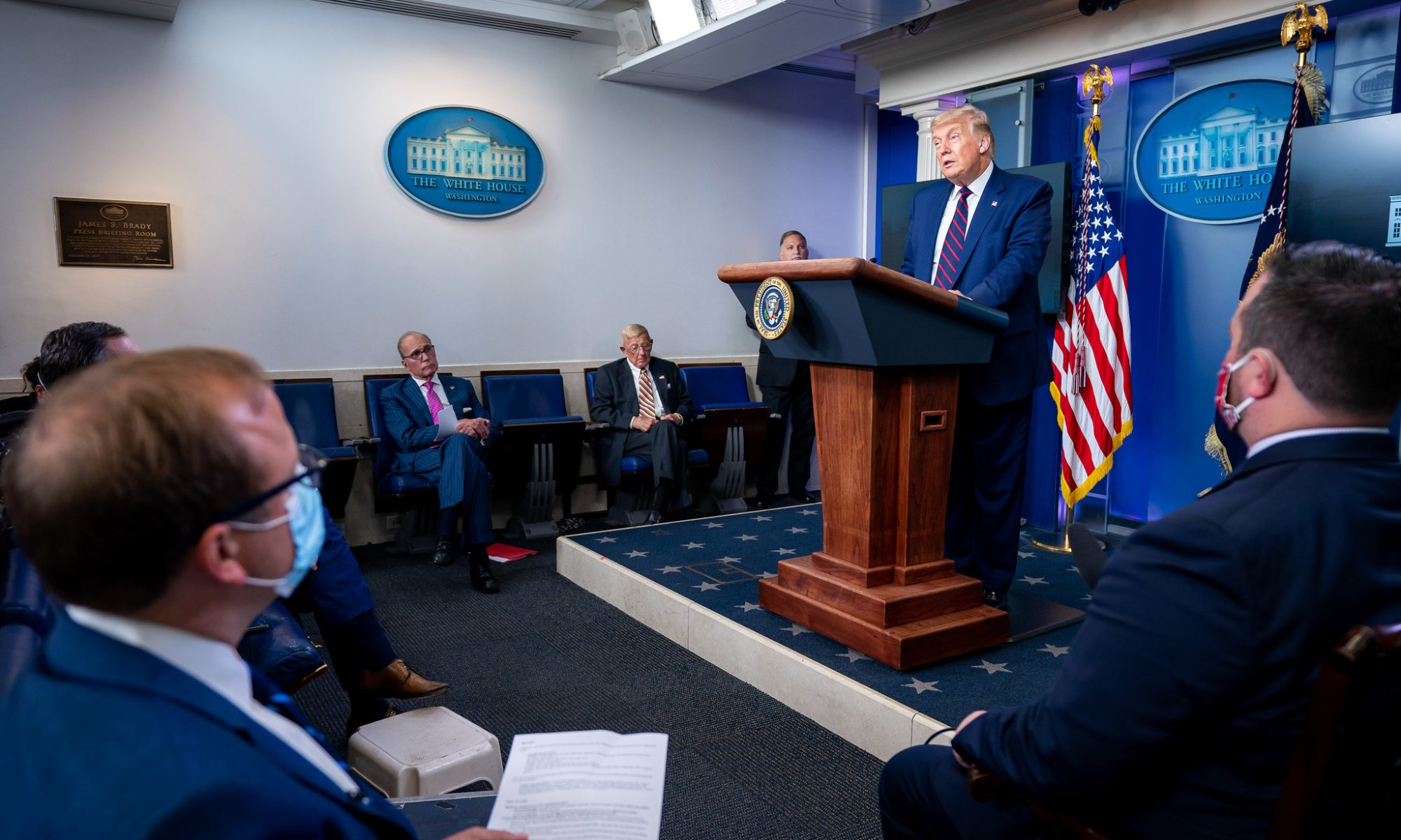Donald Trump delivers a press briefing behind a wooden podium to a group of reporters.