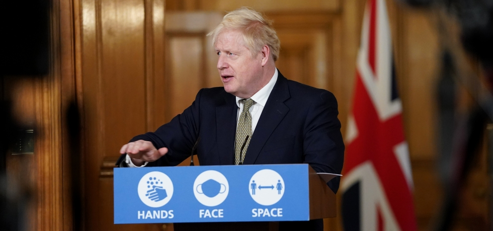 Boris Johnson stands behind a blue podium which says 'Hands, Face Space' on it.