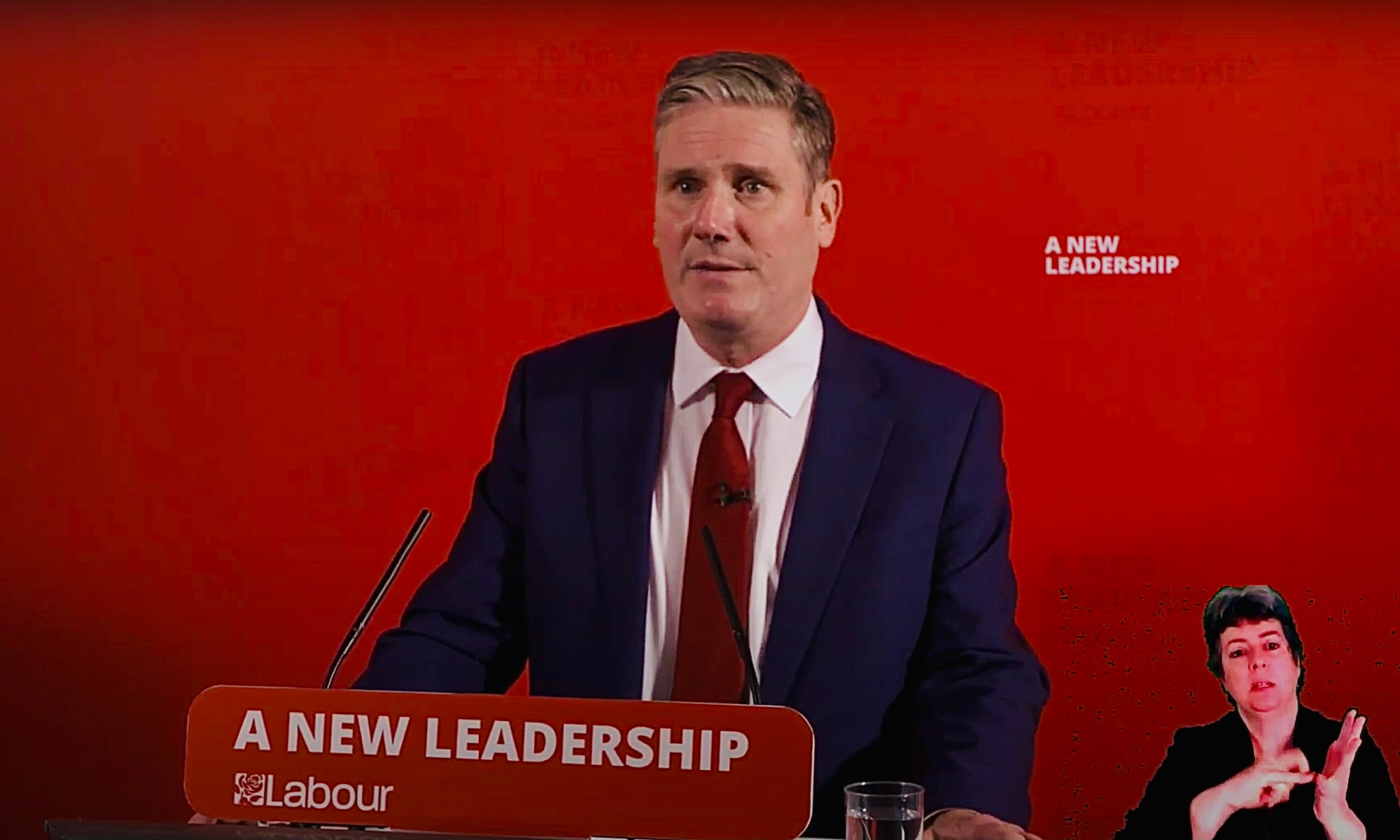 Sir Keir Starmer behind a podium with the words 'A New Leadership' on it. A BSL interpreter is visible in the bottom right.