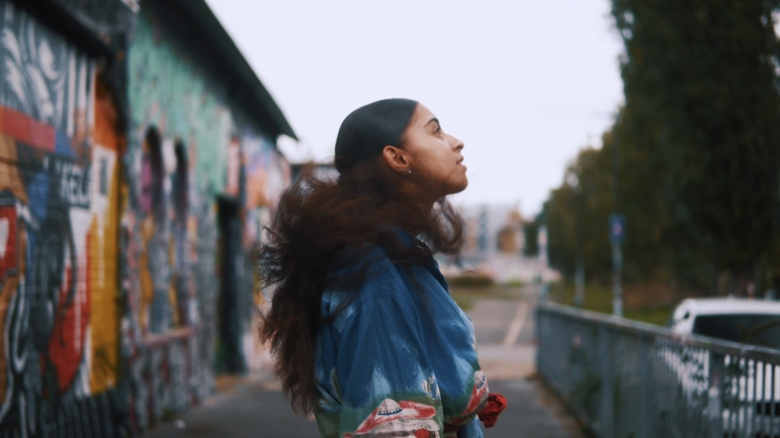 Girl in blue top and with frizzy hair. She's looking up at the sky and the photo is taken to her right. Behind her is a metal building which is covered in colourful graffiti.