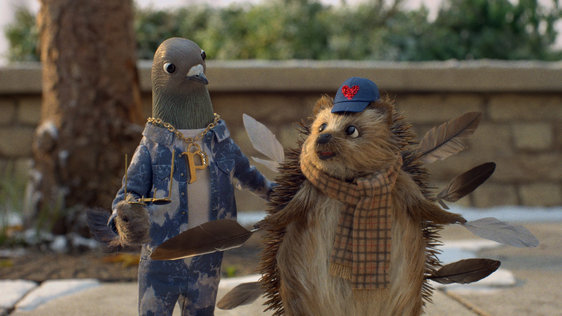 A 3D animated pigeon on the left, wearing a blue suit and golden chain with the letter P on it, smiles at a hedgehog who has a blue cap with a red heart on it. He's holding two brown feathers, and has several more attached to his spiked back.