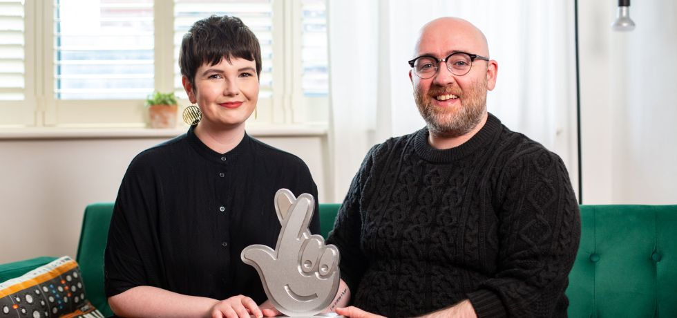 Megan (left) and Sean (right) sitting on a green couch holding their silver National Lottery award.