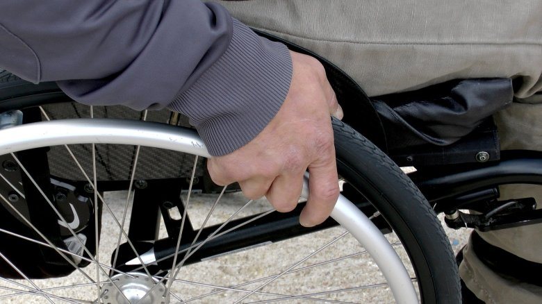 Man grasping the right wheel of his wheelchair.