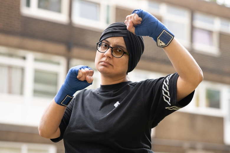 A woman wears a black headscarf, glasses and a black shirt. She has wraparound boxing gloves around her knuckles and wrists, which are raised in a fighting pose. Behind her are a block of flats.