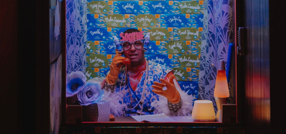 A man in a booth holds a telephone. He wears rubber gloves on his hands and a floral gown. A wall of tissue boxes is behind him, and he wears paper glasses with the word 'soothe' on it, and two hand sanitisers either side.