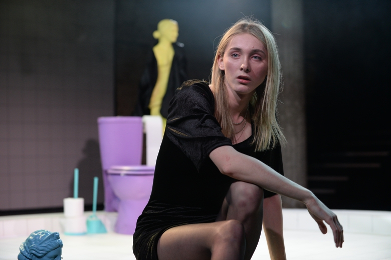 A white woman with blonde hair and a black dress crouches on stage and looks to the right at something off-camera. Behind her is a purple toilet and a yellow mannequin.