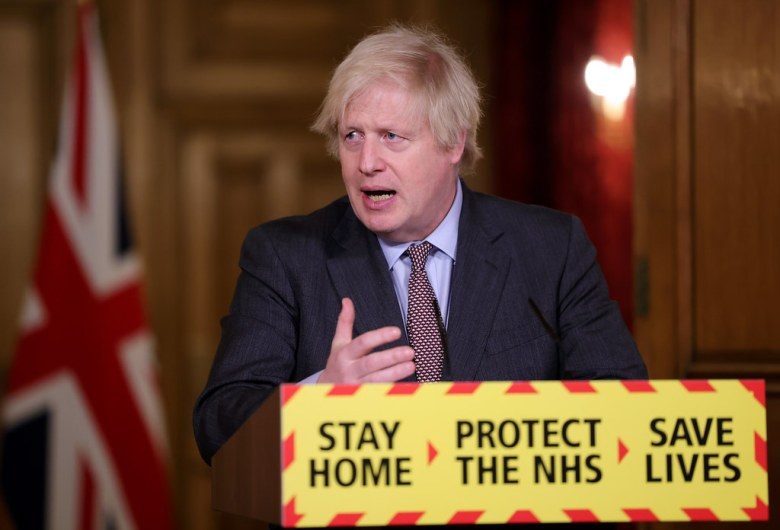Prime Minister Boris Johnson behind a podium which reads 'Stay Home, Protect the NHS, Save Lives'.