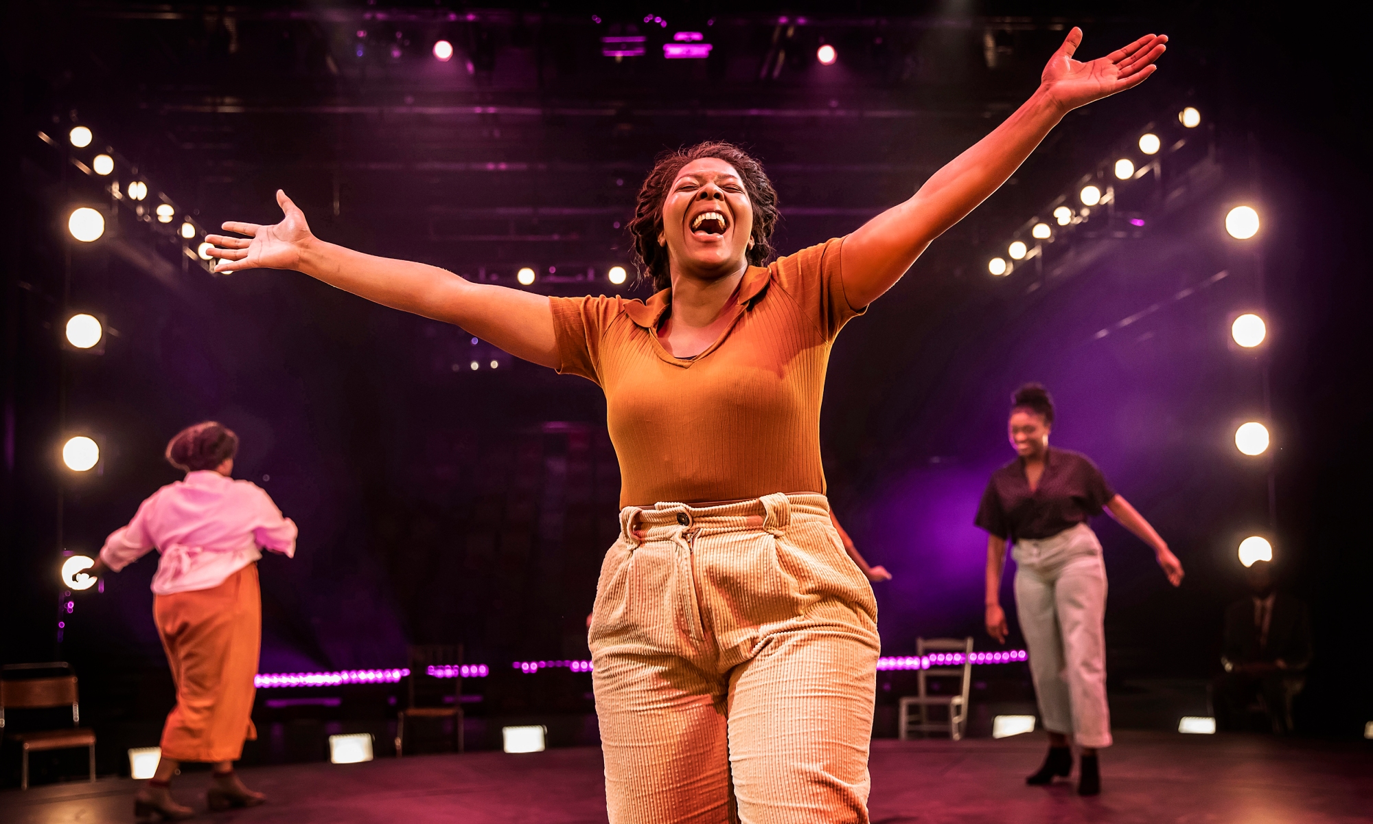 T'Shan Williams, a black woman, stands on stage in a brown top and white trousers. She is singing, smiling, with her arms outstretched.