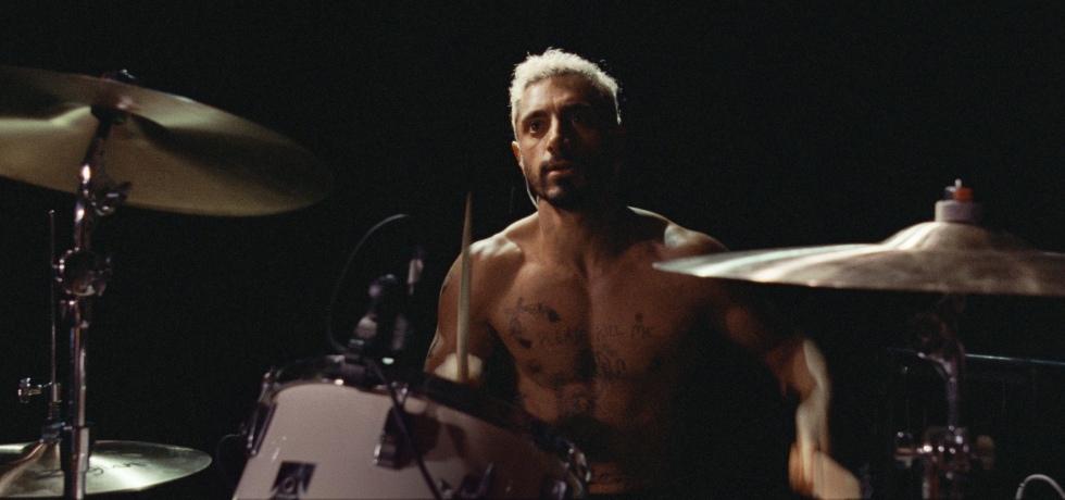 Left, Riz Ahmed, a British Pakistani man, sits half naked behind a drum kit.