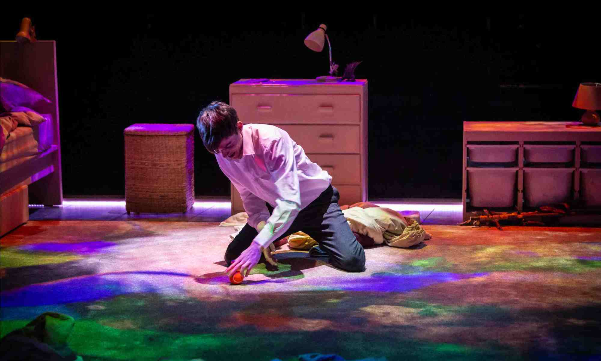 A white teenager in school uniform (white collared shirt) kneels and plays with a ball in his bedroom, the floor of which is lit up in multicolour.