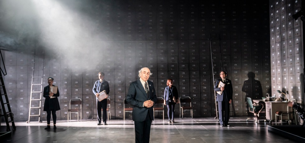 A white man in a suit stands centre stage. At the back new dose people holding folders. They stand against a wall of drawers.