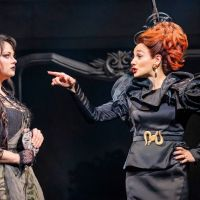 On the left, a young white woman, Cinderella, wears black rags. On the right, an older white woman, the Stepmother, with a black dress and curly, bright ginger hair points at her.