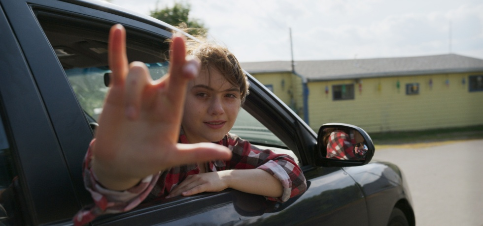 A young blonde girl leans out of a car and shows her right hand with her thumb, pinky, middle and index fingers sticking up. The middle and index are crossed. It's a take on the sign for 'I love you' in sign language.
