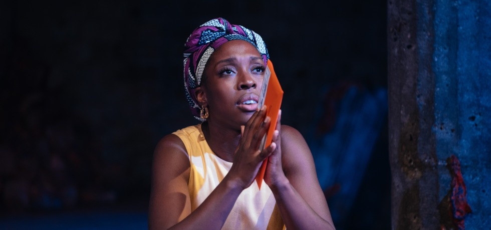 A Black woman with a bright blue and purple headdress and yellow dress sits and clasps a red envelope with both hands. She stares upwards, intensely.