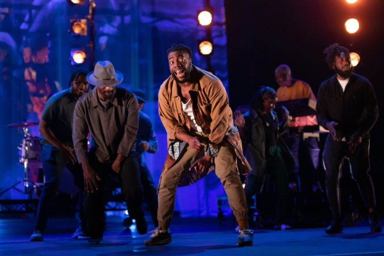 Fehinti Balogun, a young Black man, crouches with other dancers as he dances on a stage.