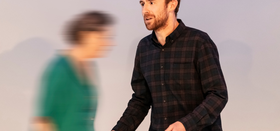 A white man with short brown hair, a moustache and beard and black chequered shirt, has his arms out in front of him. In the background behind him, blurred, is an older white woman with grey hair in a green dress, moving right.
