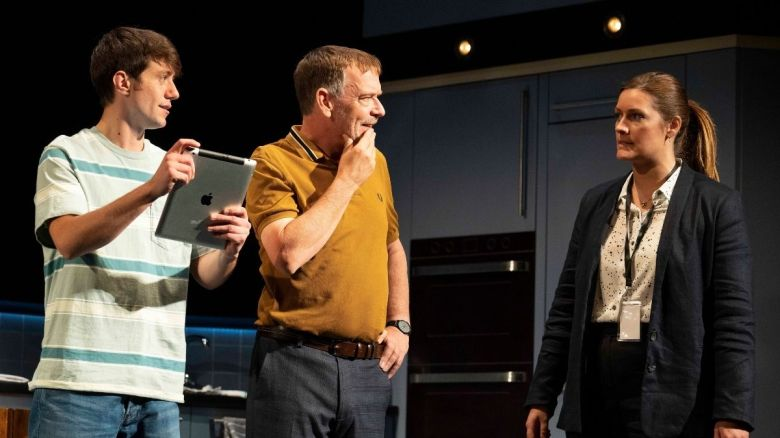 From left: a young white man in a striped white shirt holds an iPad, an older white man in a yellow shirt massages his chin, and a woman in a black jacket, white shirt with a police lanyard.