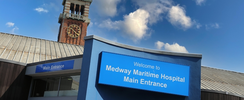 'Welcome to Medway Maritime Hospital Main Entrance' sign on building against blue sky.