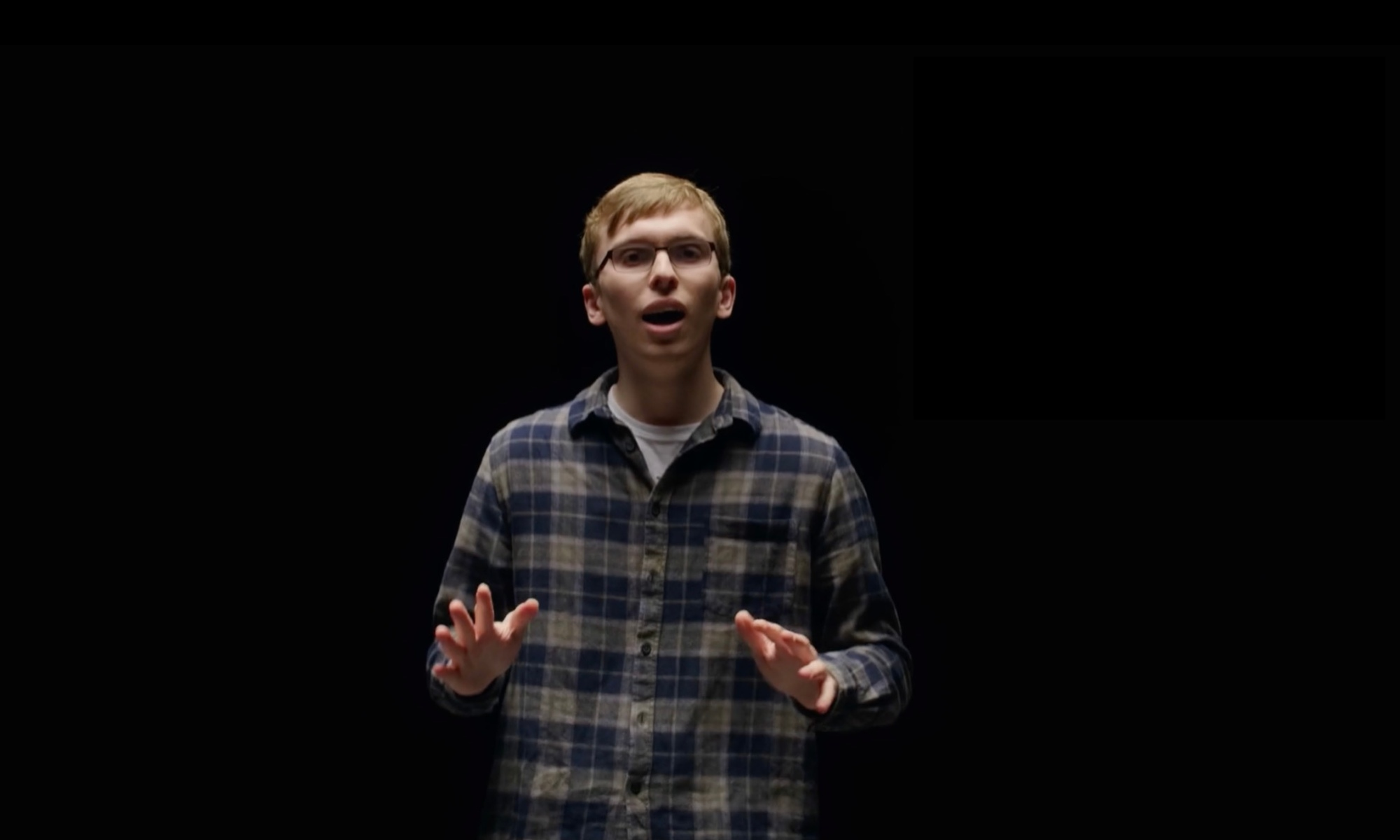 Liam wears a green and blue checkered shirt, and stands against a black background. He has his arms outstretched in front of him.