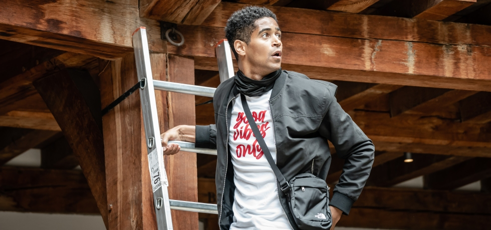 Alfred Enoch, a Black man wearing a black bomber jacket and white shirt with the text 'good vibes only', stands on a ladder affixed to the side of Shakespeare's Globe.